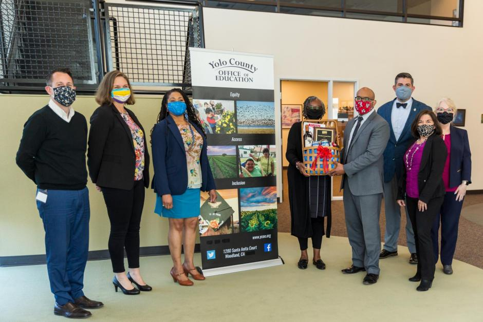 Photo of 7 adults, professionally dressed with Yolo County Office of Education banner visible