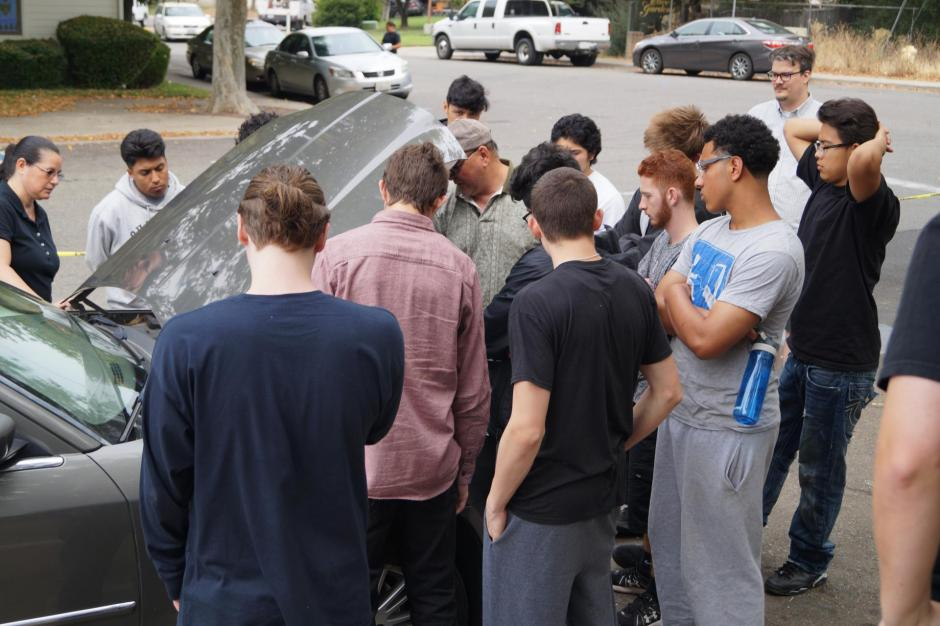 Teenage boys gathered around a car looking under its hood.