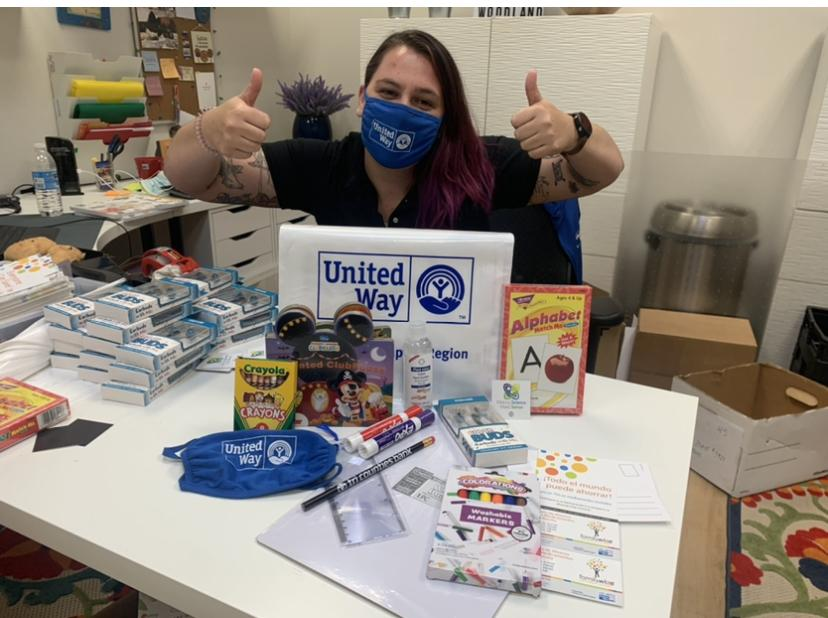 Young white woman appearing wearing a blue United Way logo mask with both thumbs up. Various school supplies on the table in front of her.