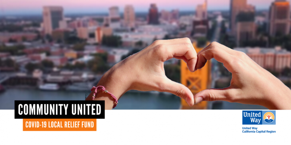 hands making a heart shape with the Sacramento skyline in the background