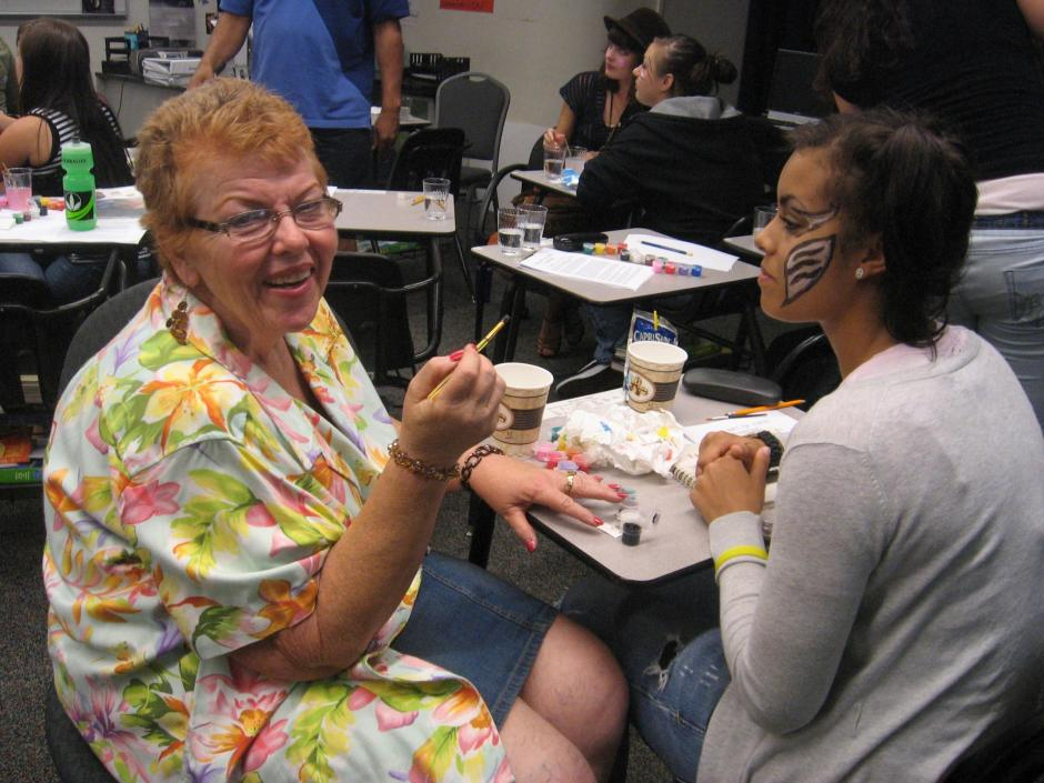 An older white woman painting a teen Latina's face.