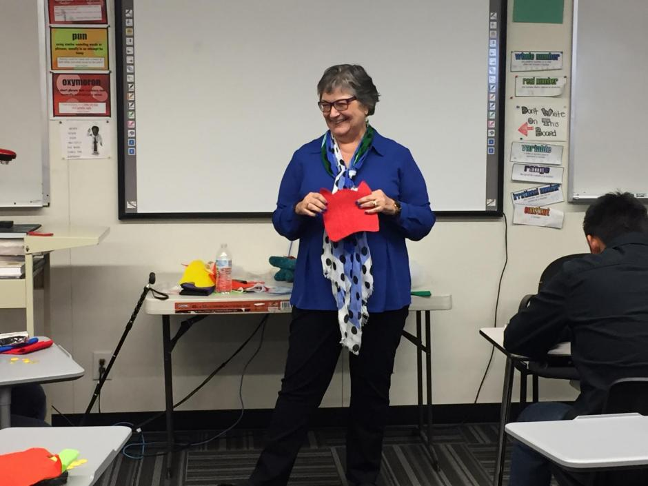 Older white woman at the front of a classroom, holding a bright red object.