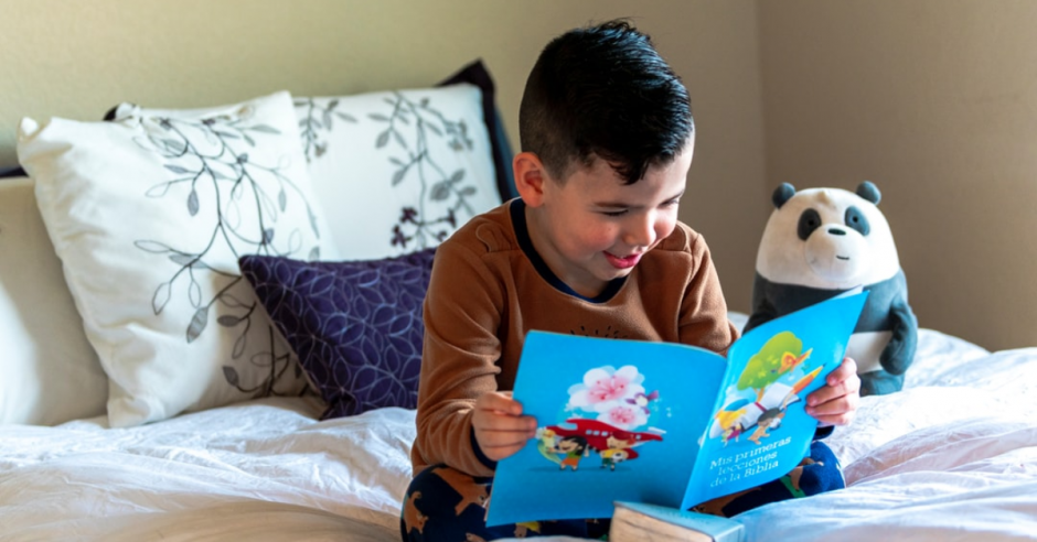 Latino boy reading a Spanish book from his bed.