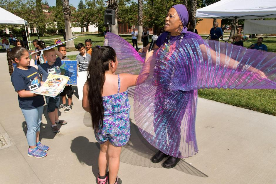 "Photo of a woman in purple outfit with tulle ""wings"" with arms out. Kids surrounding her."