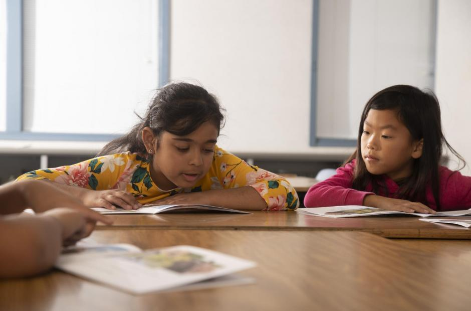 Two school-aged girls of color reading