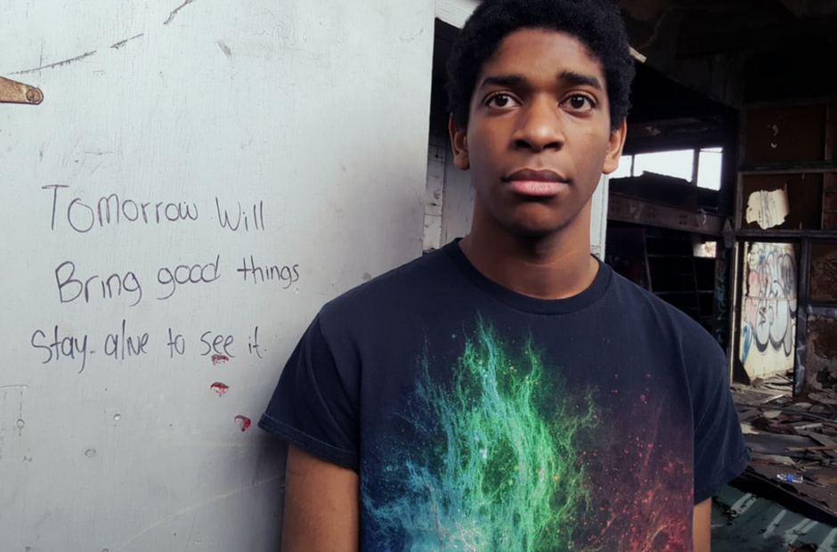"Photo of a young Black youth wearing a black tee shirt. Written message on the wall behind him reads, ""Tomorrow will bring good things. Stay alive to see it."""