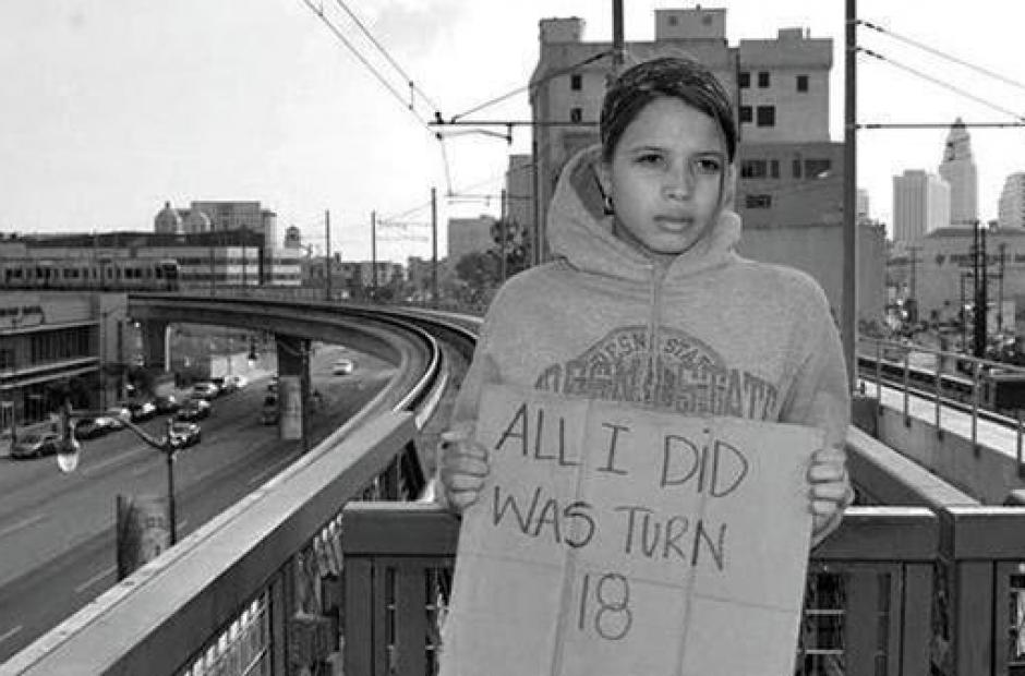 "Black and white photo of a teen girl holding a sign that reads, ""all I did was turn 18"""