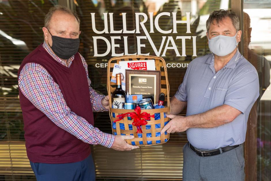 Two elder white men appearing, wearing masks and holding a gift basket. Window with signage: Ullrich Delevati visible