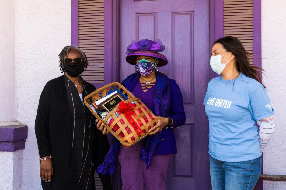 Two Black women wearing masks, one holding a gift basket, one white-Filipina with a blue LIVE UNITED tee shirt wearing a mask. Purple door in the background.
