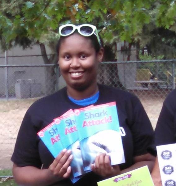 Brandi showing off some books that were labeled during the summer Campaign for Grade level Reading project.