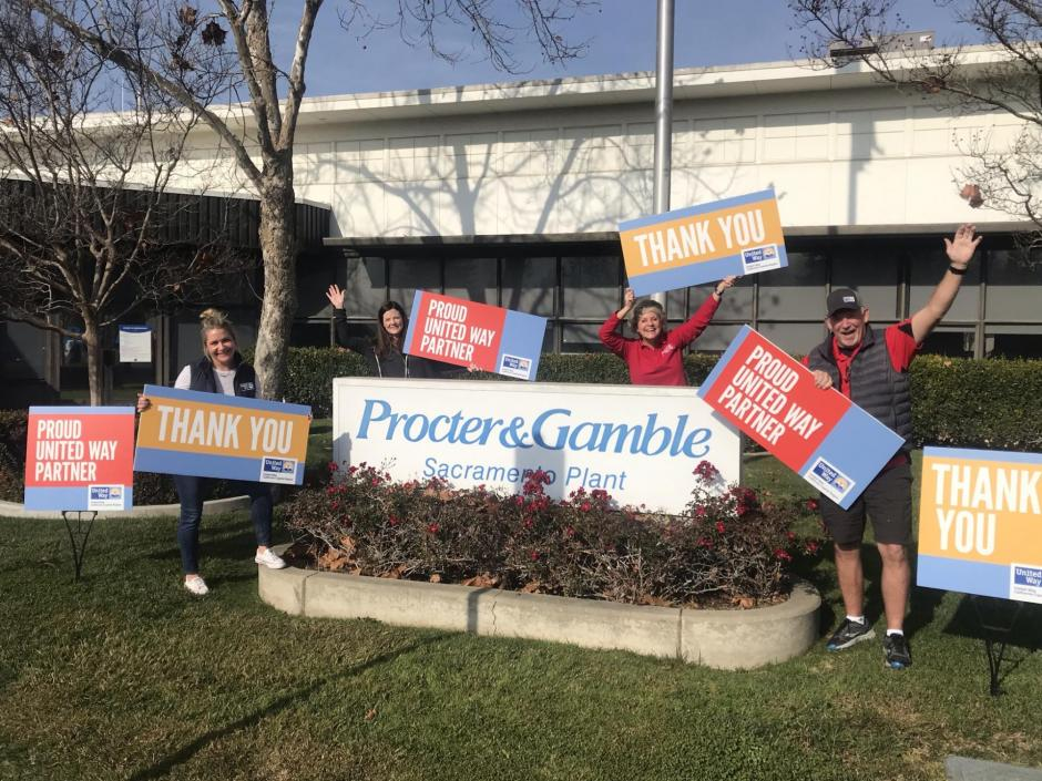 "Photo of 4 people standing next to the Procter & Gamble Sacramento building with signs that read, ""Proud United Way Partner"" and ""Thank You"""