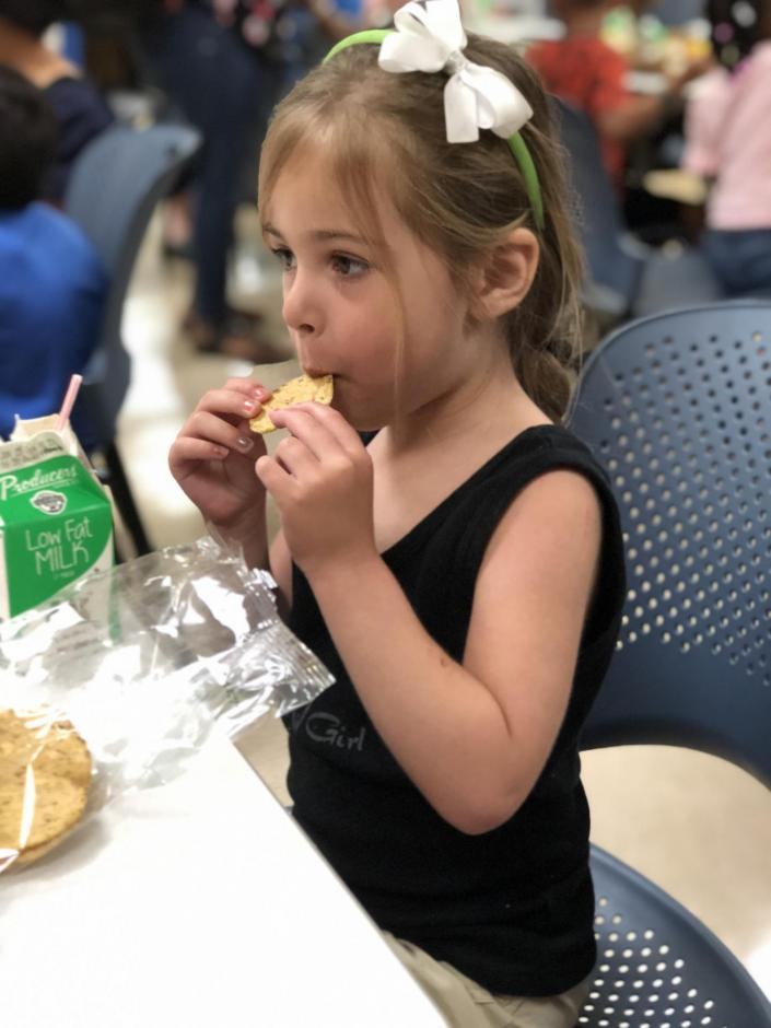 Young girl with a bow in her hair, eating a sandwich.