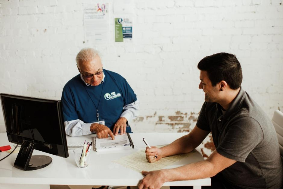 An older man in a blue tee shirt at a computer talking to a young man writing on paper.