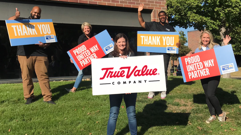 "Photo of 5 peolple with signs that read, ""Proud United Way Partner"" and ""Thank You"" with one sign in the center that has the True Value logo"