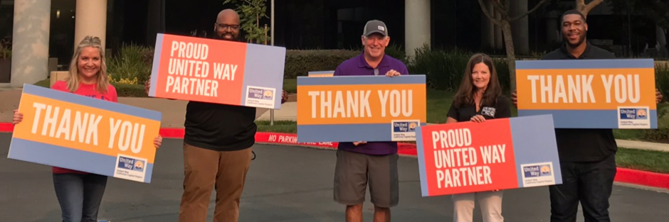 "Photo of 5 people holding signs that read, ""THANK YOU"" and ""PROUD UNITED WAY PARTNER"""