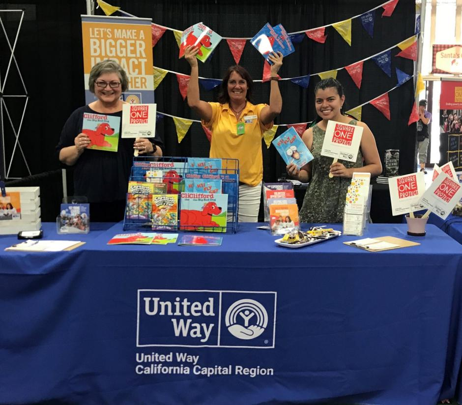 Photo of three women at a United Way booth, holding materials smiling.